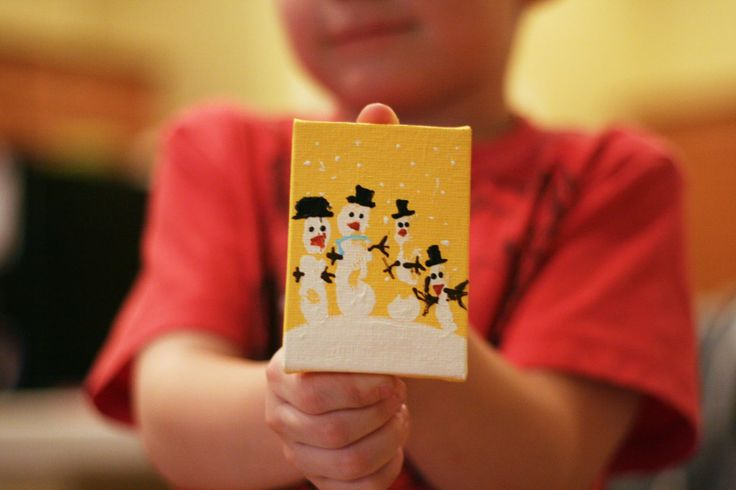 Finger print snowmen on mini canvas ornament.  The tutorial shows one child's fingerprints, but it would be neat to do a finger print from each member of the family, for sort of a family of snowmen!