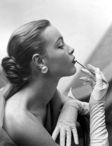 Model applying lipstick, vintage photograph