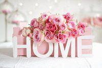 Rosa Rosen in gestrichener Obstkiste und Deko-Buchstaben 'HOME'