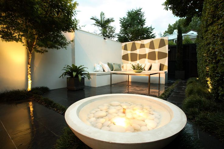 white cement water fountain bowl with white stones inside and lit. Courtyard Garden | Paddington