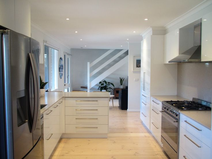 Everything in its Place - Contemporary white and gray kitchen, clam shell Caesar Stone bench and splash back with lime washed timber floors