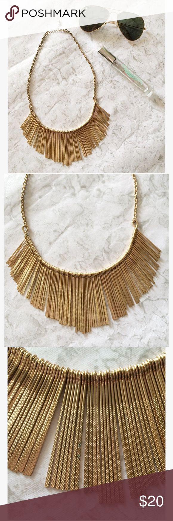 """Gold Fringe Necklace A golden fringe necklace, with textured matchstick fringe. Bib necklace fit, with adjustable length. Condition: gently pre-loved. Very minor discoloration on one side (the """"back"""") and back of the chain. Stock photos show actual necklace. Model photo shows similar necklace and styling suggestion. Very similar to a matchstick bib necklace sold at Anthropologie! Considering ALL offers on makeup and jewelry bundles! Feel free to """"lowball."""" Jewelry Necklaces"""