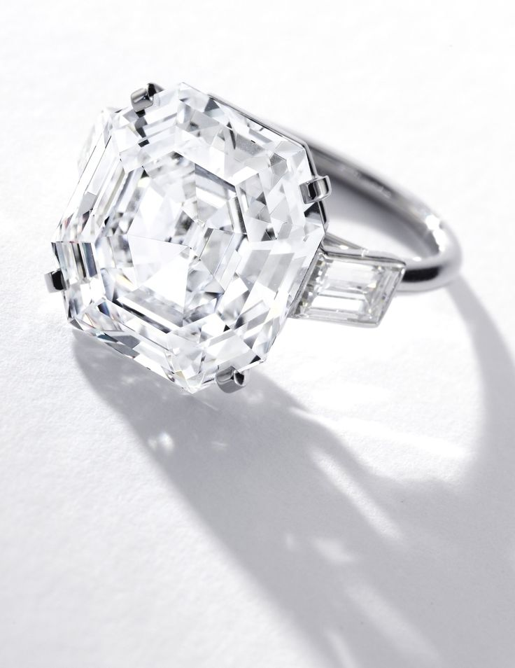 Very Fine Diamond Ring, Cartier. Set with a 13.60 carat cut-cornered rectangular step-cut diamond, flanked by two baguette diamonds, mounted in platinum.