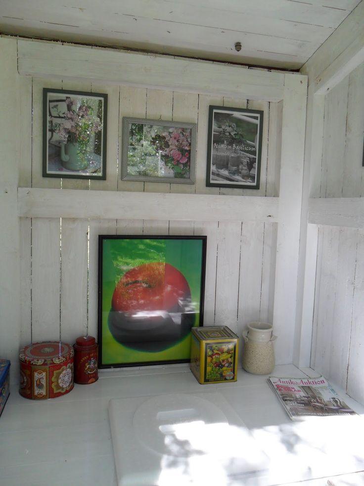 vitmålat utedass med tavlor och kakburkar