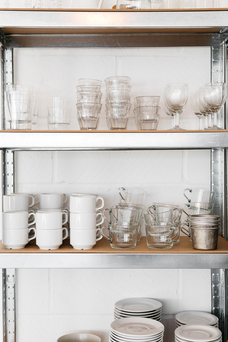 Clear glass tumblers and white ceramic teacups and saucers on stainless steel industrial shelves at the Rye London kitchen