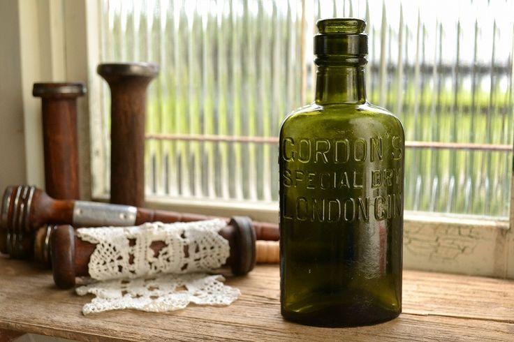 写真の商品は、お店やお部屋のインテリアにおすすめの「オリーブグリーンのアンティークボトル 大きいサイズ ゴードン/ジンボトル」です。