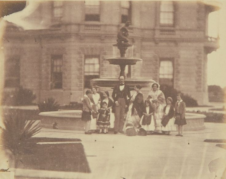 May 24, 1854 Left to right, standing in front of fountain outside Osborne House: Prince of Wales, Princess Royal, Princess Alice, Prince Arthur (in front of Princess Alice), Prince Albert, Queen Victoria, Princess Louise, the Duchess of Kent, Princess Helena & Prince Alfred. Dandie & Deckel, two dogs, are at the Queen's feet.
