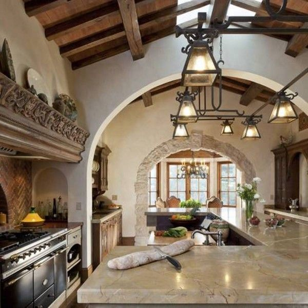 Beautiful Mediterranean kitchen, stone archways, tan marble countertops and island, lantern lighting.