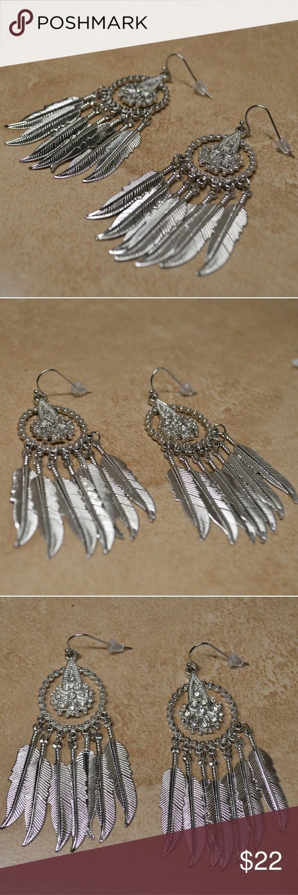Stunning Brand New Silver Dreamcatcher Earrings These beauties are a great find! Shiny silver with dazzling jewels add sparkle to any outfit. Dangly feathers at the bottom of each dreamcatcher.  These are brand new and perfect!     Tags feathers feather boho bohemian hippy earrings dangle dangly native American Indian web silver round hippy classy girly hook earrings Boutique Jewelry Earrings