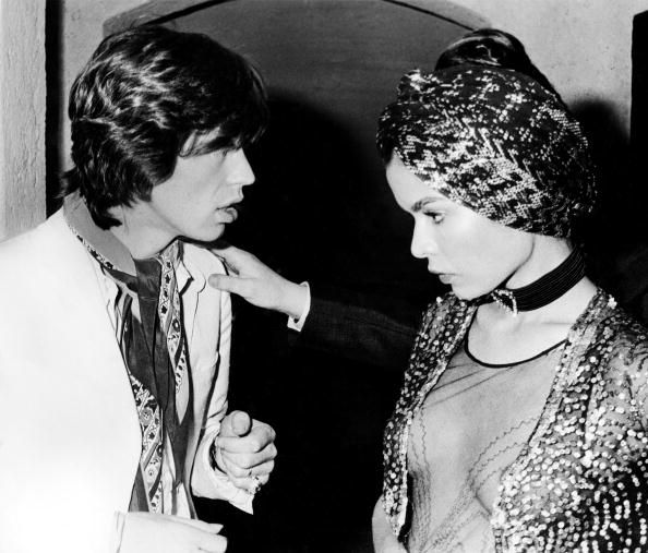 Mick Jagger talking to wife Bianca Jagger at a party in St Tropez (Photo by RB/Redferns)