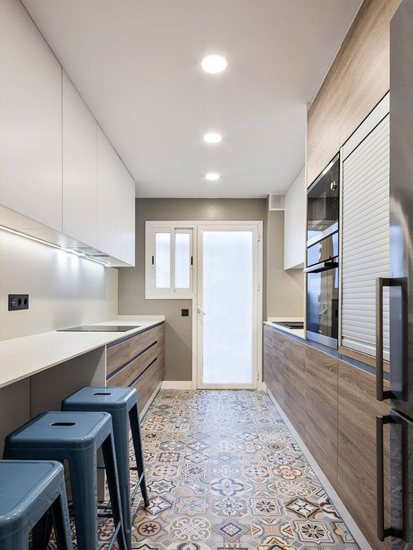 Modern apartament. The layout of the kitchen con two paralelo fronts. The furniture is attached to the walls. The surface of the kitchen doubled and small bar as incorporated for eat.