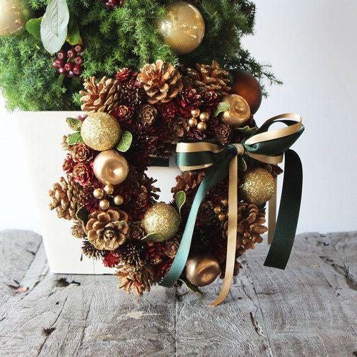 たくさんの植物の実とゴールドのリンゴをメインにデザインされた、シックな雰囲気のクリスマスリースです。ドアに掛けたり、テーブルに置くなど、ご自宅のインテリアに合わせてさまざまな楽しみ方ができます。サンタさんの袋のような、赤のラッピング袋に入れてお届けします。※お届けする商品はリースと、リースを吊るすドアハンガーのみです。※2016年11月7日(月)以降のお届けになります。