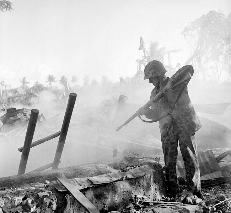 W. Eugene Smith: American soldier pointing rifle into bunker during fighting in final days of invasion. Saipan, Marianas Islands, 1944