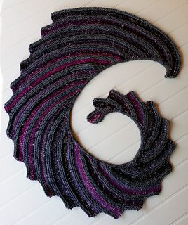 Inspired by the classic Hitch-Hiker shawl, this shawl features two colors which are alternated using a short section worked in Intarsia. An i-cord border accents the spiral like curve of the top border which wraps snugly around the neck and gives the shawl a touch of elegance.
