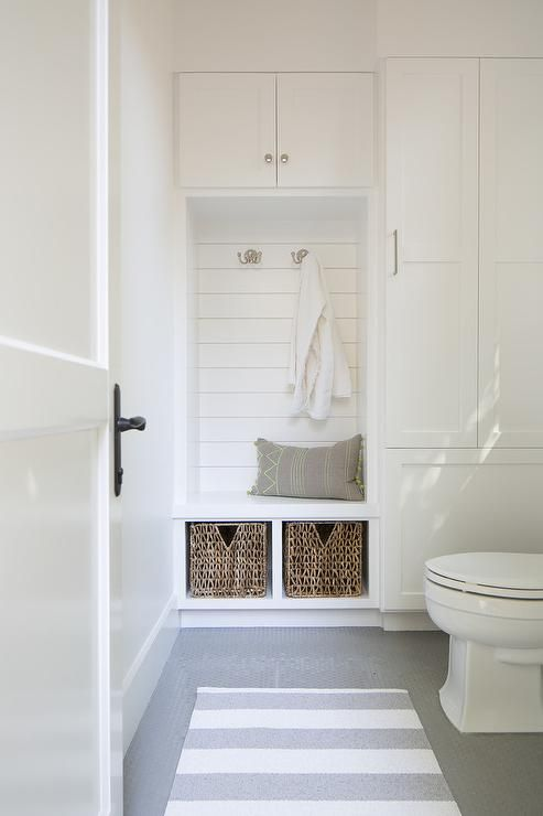 Bathroom in mudroom features an under window toilet alongside a white and gray stripe rug layered atop a gray penny tiled floor.