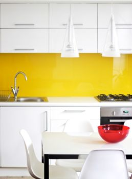 ♥Yellow glass splashback | This simple white kitchen is transformed by one bold feature - a spell-binding yellow glass splashback. Genius! | yellow décor ideas | modern white kitchen ideas | splashback ideas