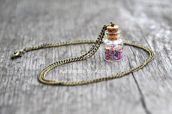 Small bottle with colorful bobbles and antique bronze plated