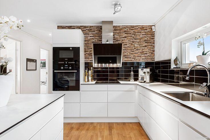 Stort öppet kök med skåps-inredning i vitt från Ballingslöv, svart kakel ovan diskbänken och vita köksbänkar. En köksö med bra förvaring som delar av rummet mot matplatsen.