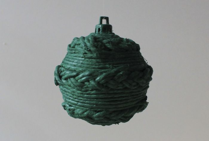 The ball wrapped with cord and braids and coloured in green.