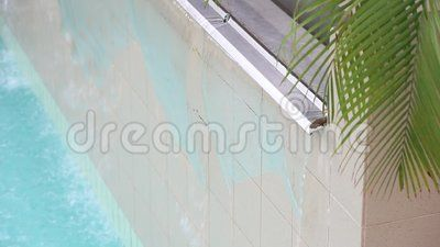 Waterfall on the wall in thermal pool and palm leaves.