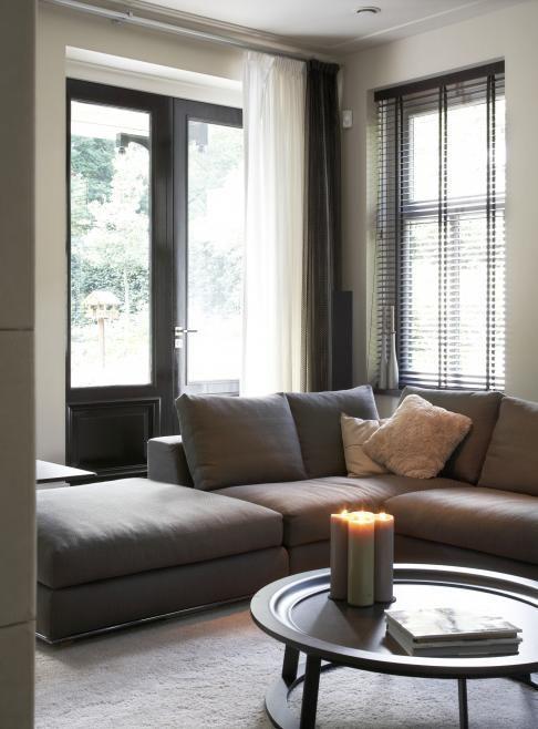 Taupe kleuren in huis gecombineerd met mooie houten jaloezieen geven een heerlijke sfeer in huis.