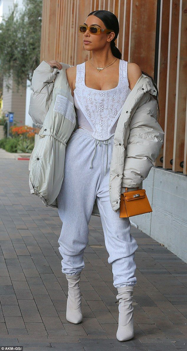 Strutted her stuff: Kim completed her look with tortoiseshell-framed sunglasses and a tan purse and wore her hair sleeked down over her skull and tied back from her face