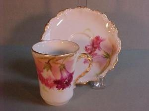 Limoges chocolate cup and saucer; handpainted coral and maroon carnations with speckled gold trim; Coiffe Mark 3, 1891-1914, on both pieces and Flambeau China Mark 4, 1890's to early 1900's, on saucer