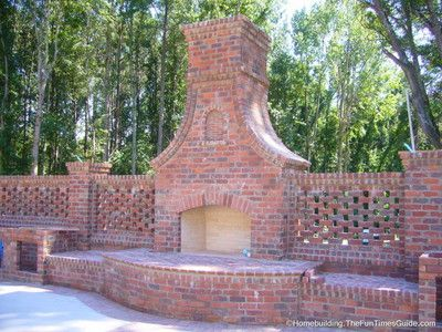 Outdoor brick fireplace flanked by a pierced brick wall.