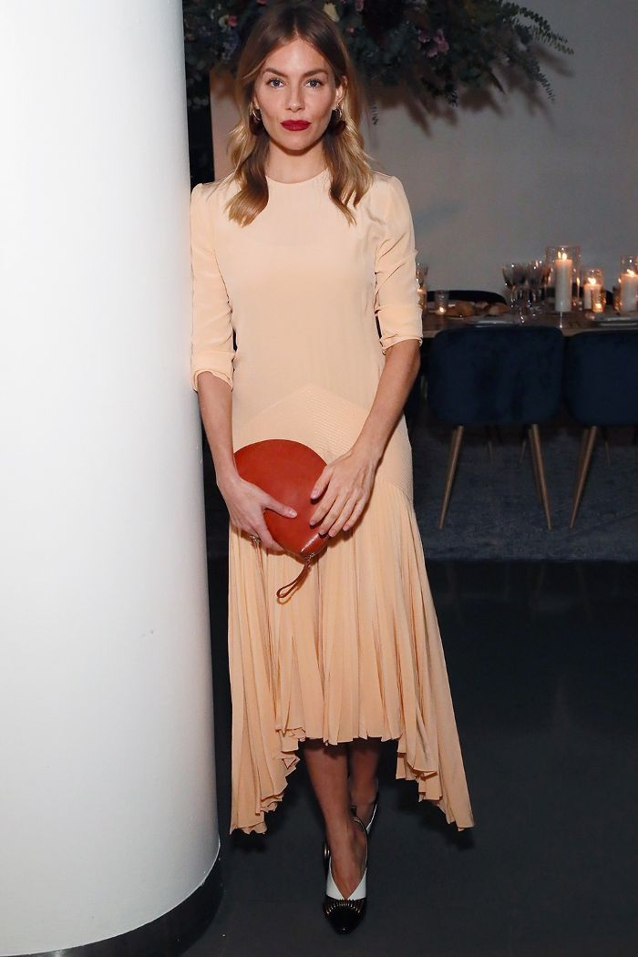 efd3c34beffe6 Celebrity party outfits: Sienna Miller in a peach midi dress with a half  moon bag