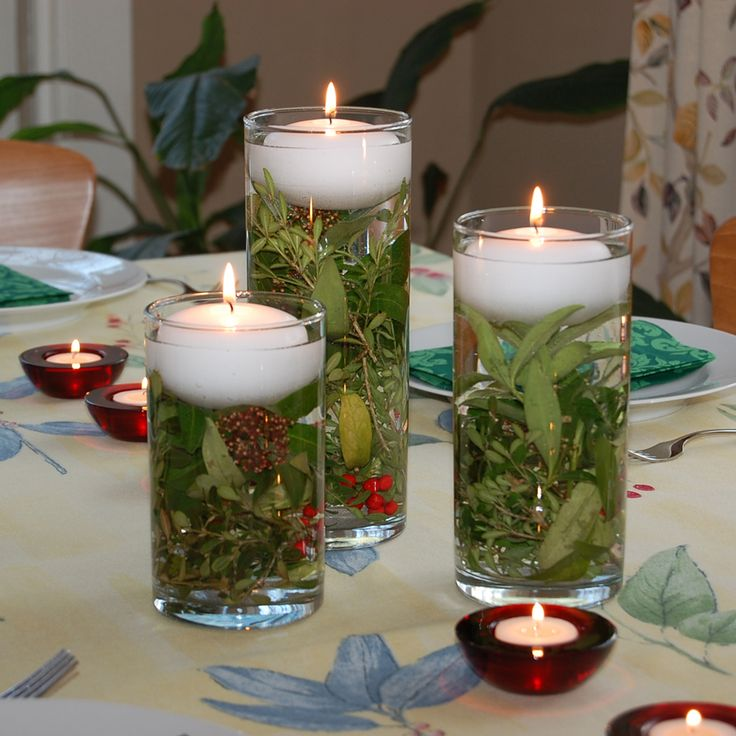 Floating candles in water filled vase and holiday greens