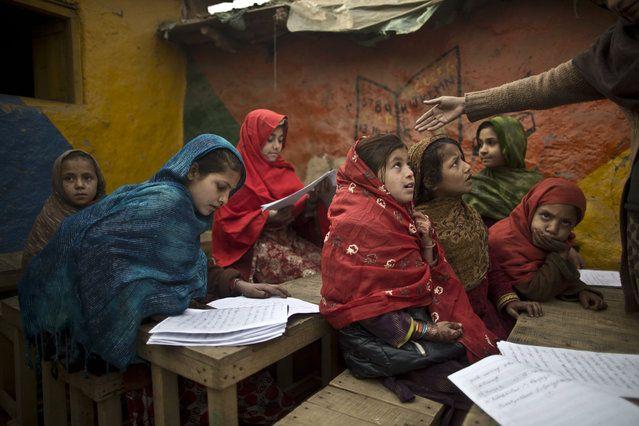 VIDA DIARIA DE AFGANOS Refugiados afganos y colegialas paquistaníes desplazados internos asisten a clases en una escuela improvisada en las afueras de Islamabad, Pakistán, Lunes, 12 de enero de 2015 niños paquistaníes y el personal regresaron a una escuela en el noroeste de Pakistán, donde hombres armados talibanes casi un mes murieron 150 personas - casi todos ellos estudiantes.  (Foto por Muhammed Muheisen / AP Photo)