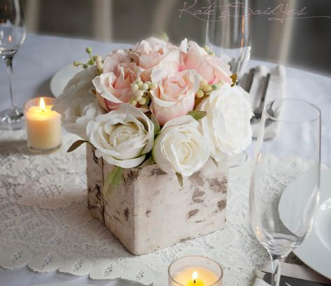 A perfect rustic rose wedding centerpiece for your special day! Romantic blush pink and ivory roses are accented with soft green berries, and sit in a rustic birch centerpiece. This arrangement measur
