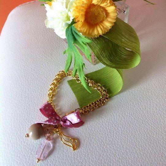 Bracciale con doppia catena dorata,fiocco color rosa antico con poi bianchi,ciondolo Gatto color oro e pietre.