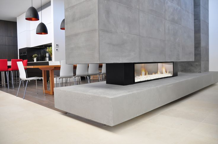 Escea DX1500 gas fireplace resting on concrete base with a blue stone surround. This fireplace has a white coal fuel bed.  escea.com
