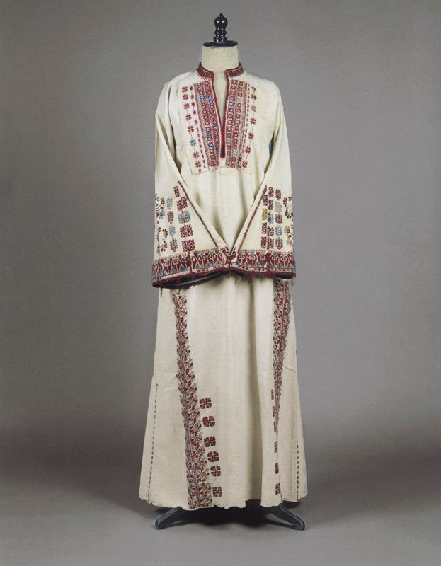 Long-sleeved chemise of off-white cotton  H. 1.28 m.  Stymfalia, Corinthia, Peloponnese. Late 19th century  © Peloponnesian Folklore Foundation, Nafplion, Greece  This chemise is part of the old type of village women's costume of Corinthia, the Argolid and probably the whole Peloponnese. It has a vertical opening at the front and is decorated with multicoloured silk embroideries of geometric motifs, and with triangular appliqués on the sleeves.