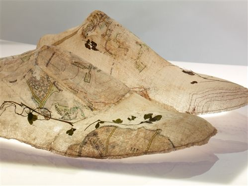 "Henny Burnett   Last Map, 2011-2012  ""Last Map"" investigates shoe lasts as three dimensional maps; the making of a last involves the mapping of the individual contours of the foot. Fragments of ordinance survey maps and contour lines are printed and sewn onto muslin and reference memories of walks and travels. Small pressed foliage is incorporated into the folds of the map, such memorabilia that has been gathered by walkers across the centuries.  muslin, size, print,thread,foliage and light…"