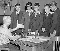 The World War II Army Enlistment Records File and Access to Archival Databases - Recruits receive applications from Staff Sgt. N. R. Kelly at the New York Recruiting Office at 39 Whitehall street in June 1940. (111-SC-115556)