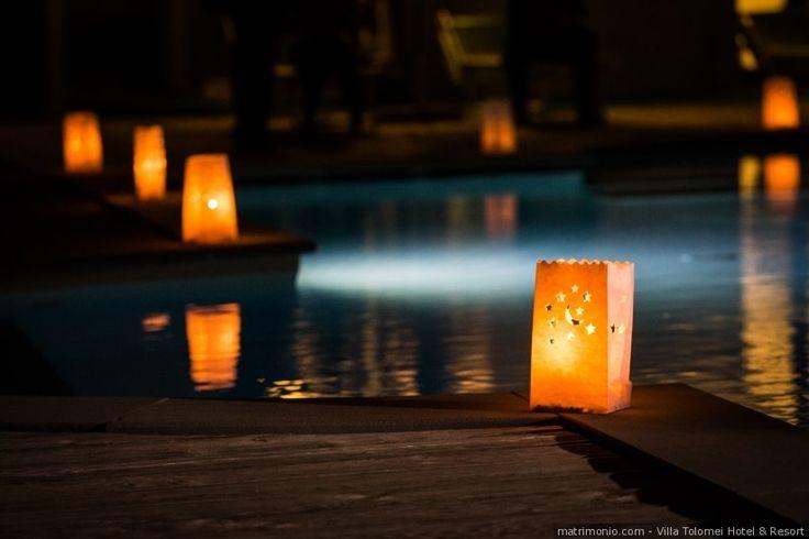 Lanterne di carta come punti di luce sul bordo piscina. Elemento decorativo di allestimento per matrimoni