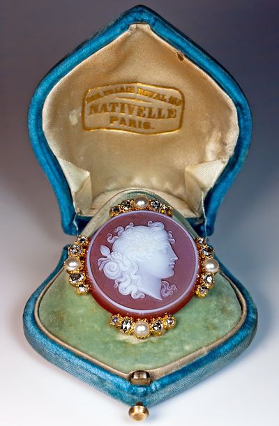 Victorian carved carnelian cameo brooch in original box. French, circa 1870, a finely carved carnelian cameo of Dionysus, the Greco Roman god of wine making and fertility, set in 18K gold bezel embellished with half pearls and rose cut diamonds, Width 37 mm (almost 1 1/2 in.), Marked with French eagle-shaped assay mark,  The cameo brooch comes in its original blue velvet retailer's case stamped in gold.
