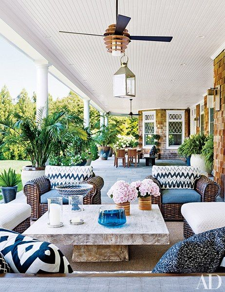 On the rear porch, wicker seating surrounds a teak table by Andrianna Shamaris.