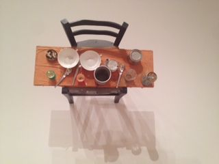 """Art at MoMA by Daniel Spoerri, Artist born Romania 1930. """"Kichka's Breakfast I 1960"""" Wood chair hung on wall with board across seat, coffeepot, tumbler, china, egg cups, eggshells, cigarette butts, spoon, cans on table."""