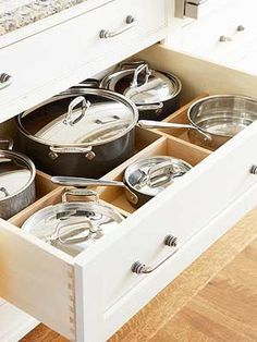 Migrate your pots and pans from a jumbled cabinet to a deep, divided drawer. Dividers provide a spot for each pan and its lid. If you're ordering custom cabinets, take into consideration the height of your largest pot plus its lid and ensure that the drawer is deep enough to accommodate it.