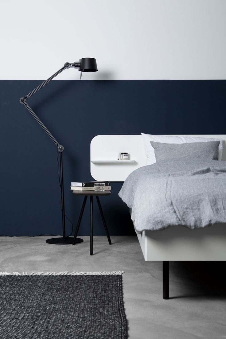 Sustainable white bed by Trecompany with grey linen bedding by By Molle. Blue wall and a little stool as a night stand.