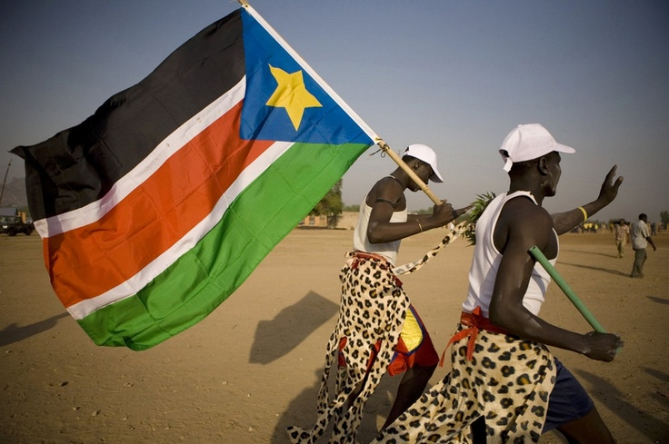 Performers in traditional garb parade the South Sudan flag in Juba ahead of the referendum