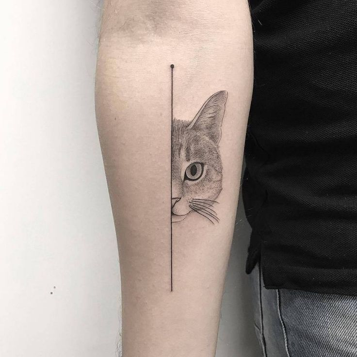 Half cat face tattoo on the right inner forearm.
