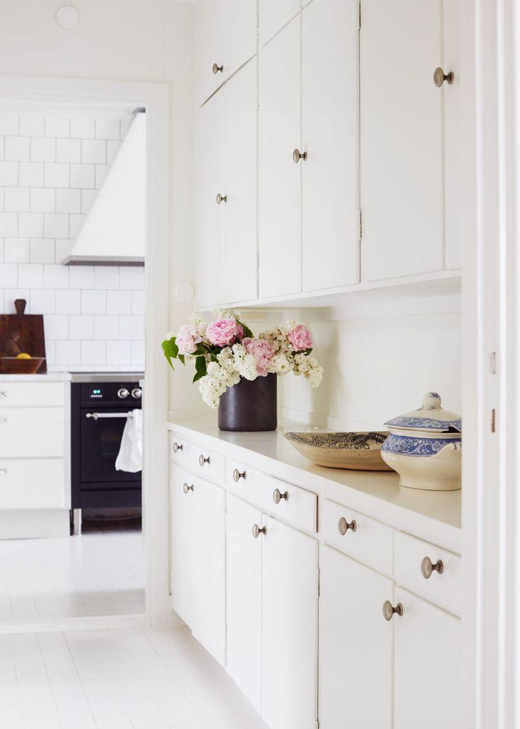 Kök med bevarad funkisstil som skapar ljus och rymd. Inspireras av de helkaklade vita väggarna och generösa bänkytorna i carraramarmor. Köket saknar dessutom överskåp som förstärker känslan av luftighet och rymd.