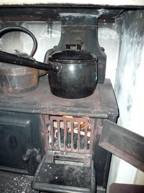 An iron cooking pan on a range in a Victorian kitchen. Look at the copper kettle in the background