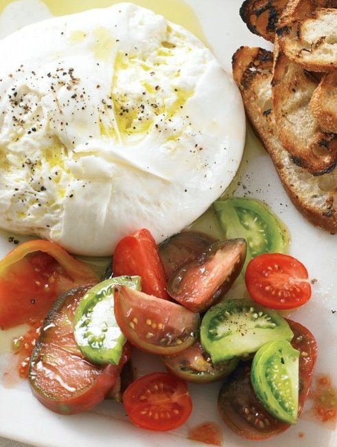 Burrata with Grilled Bread and Heirloom Tomatoes | Using burrata, a mozzarella-type Italian cheese with a creamy center, makes this appetizer particularly decadent, but you could also use buffalo mozzarella or a soft goat cheese if you prefer. In winter, substitute oil-packed sun-dried tomatoes for the heirlooms — but make the most of the fresh ones while they're still in season.