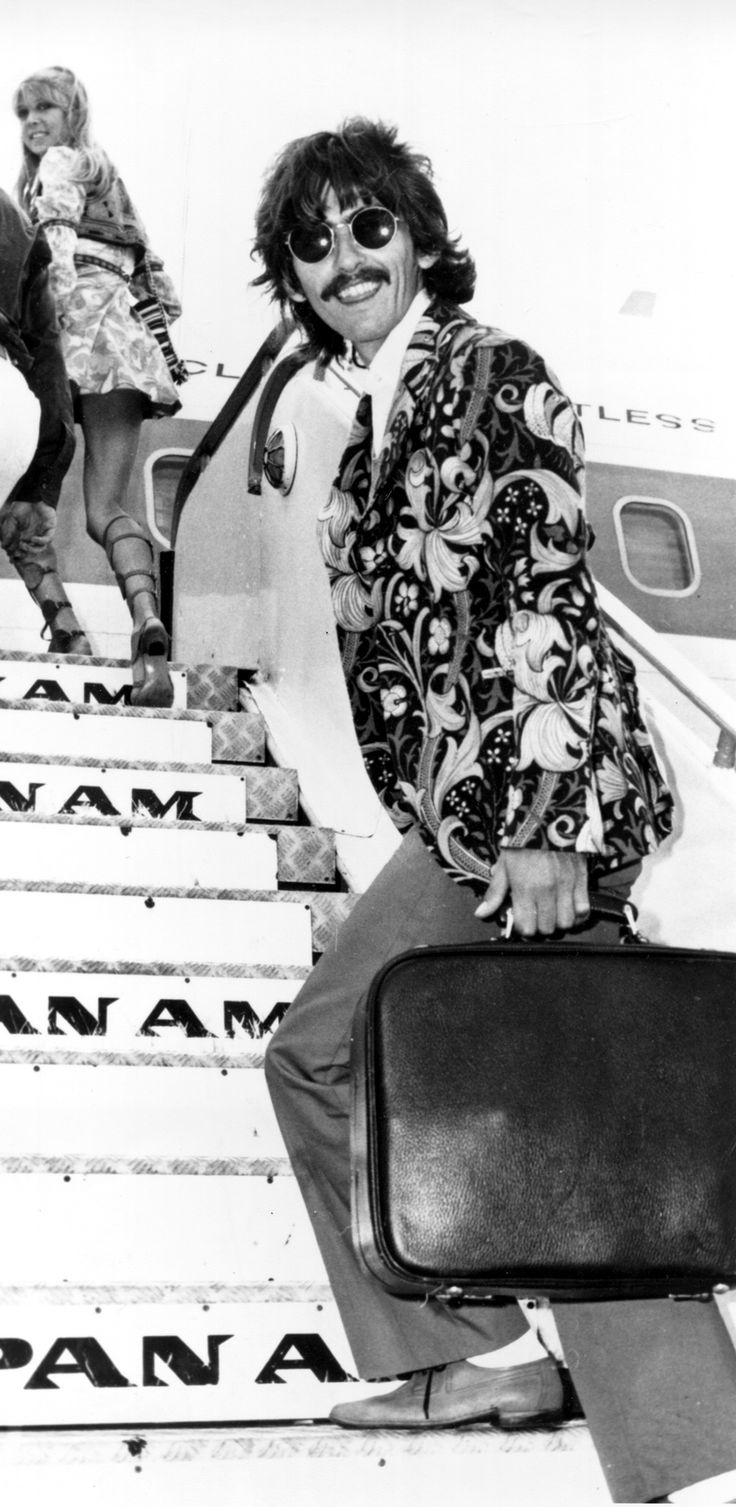 George Harrison and Pattie Boyd, board a plane at an airport in London. (Aug. 1, 1967).