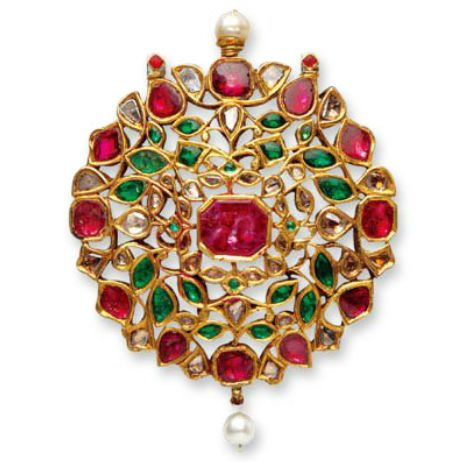 A Ruby, Emerald and Diamond Pendant, North India Jaipur (19th century) - A fine pierced pendant set with rubies, emeralds and diamonds in the kundan technique. The central rectangular ruby is surrounded by diamond petals then by a row of emerald petals and the outer rim is alternating rubies and diamonds. The pendant is mounted with two basra pearls. Fine enameling to the reverse.